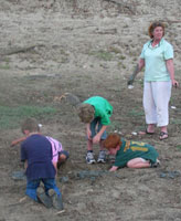 Julie McClure showing cricket fielders how to find certified organic mussels